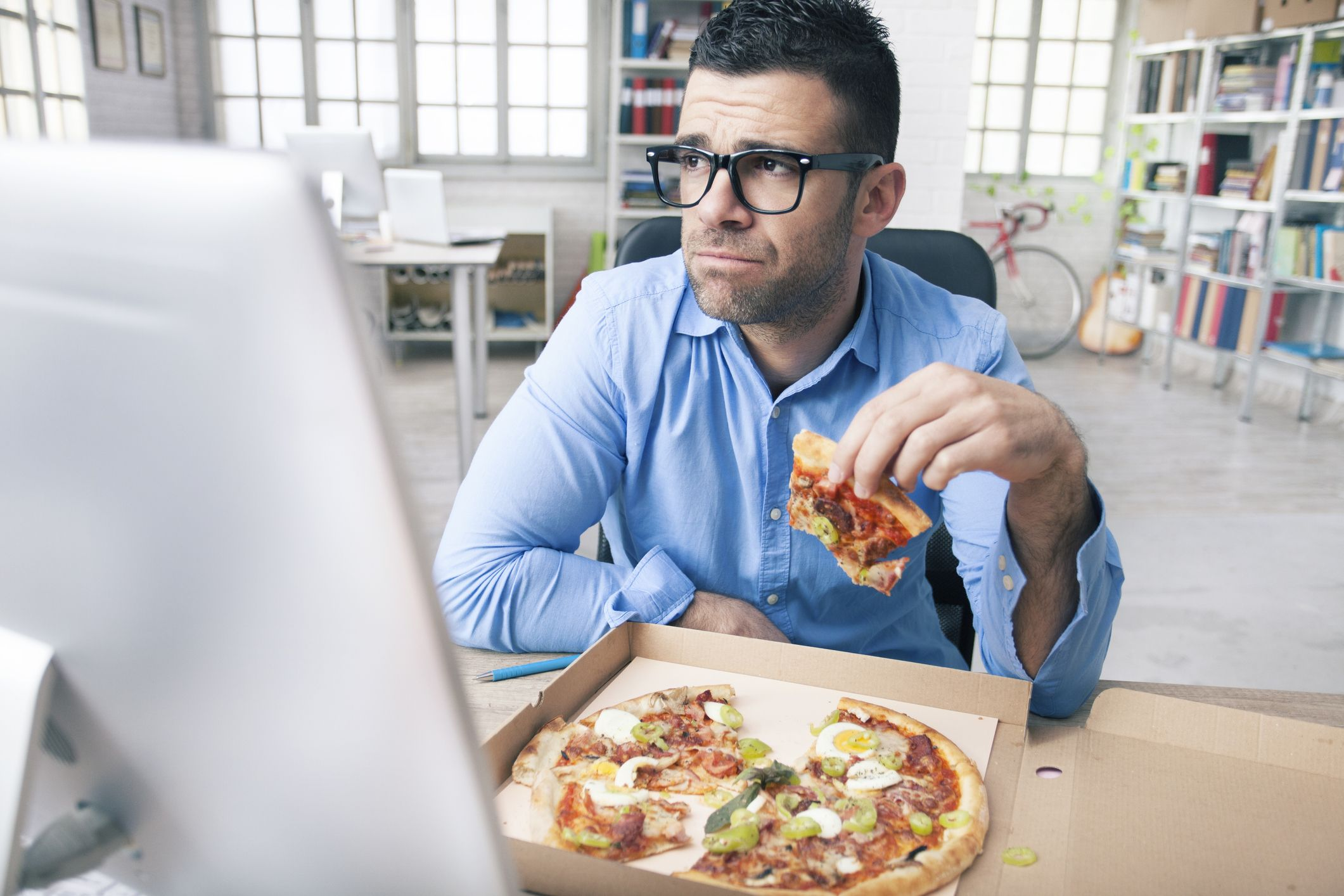 Tired businessman eating pizza at the office
