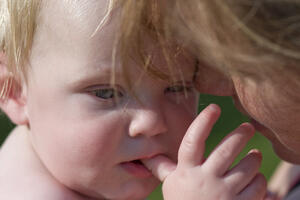 A toddler teething and chewing on her thumb