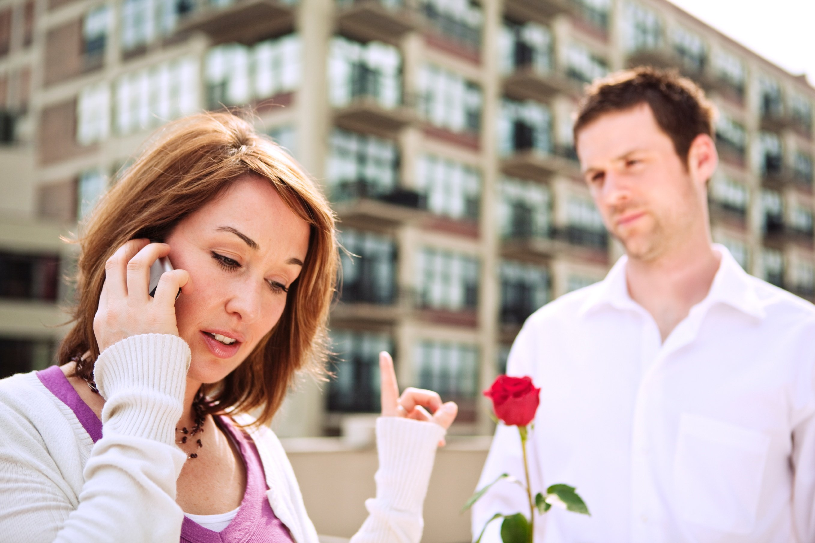 A woman on her phone unaware that her partner is holding out a rose to give her
