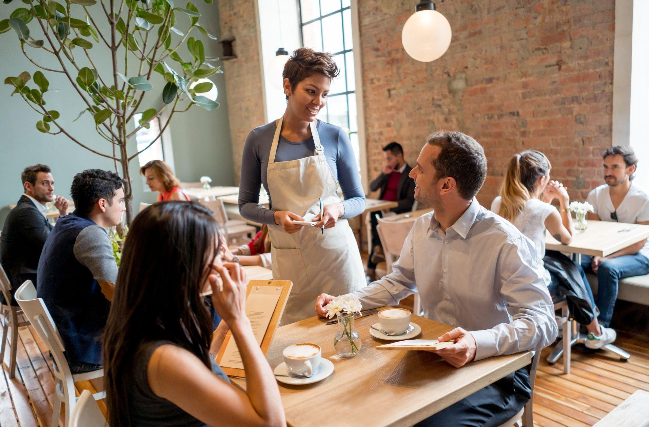 Waitress serving a couple at a restaurant