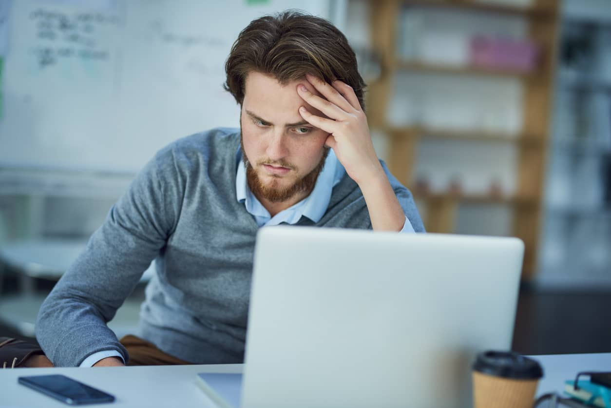 Man upset with himself for procrastinating at work