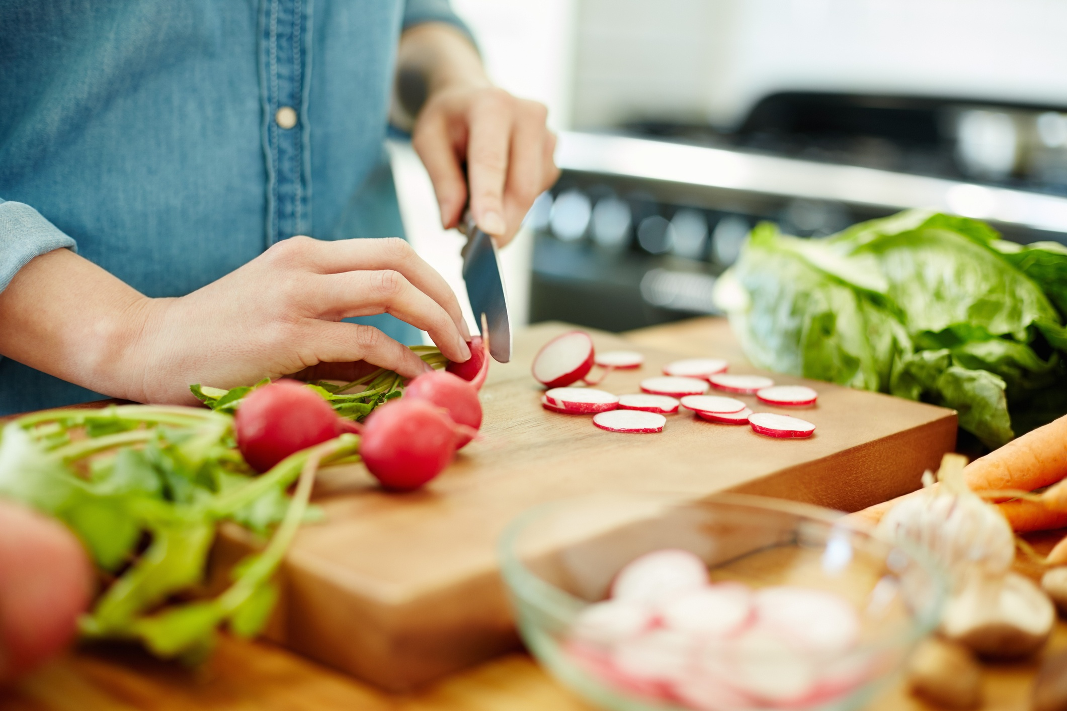 Woman chopping red radishes in the kitchen