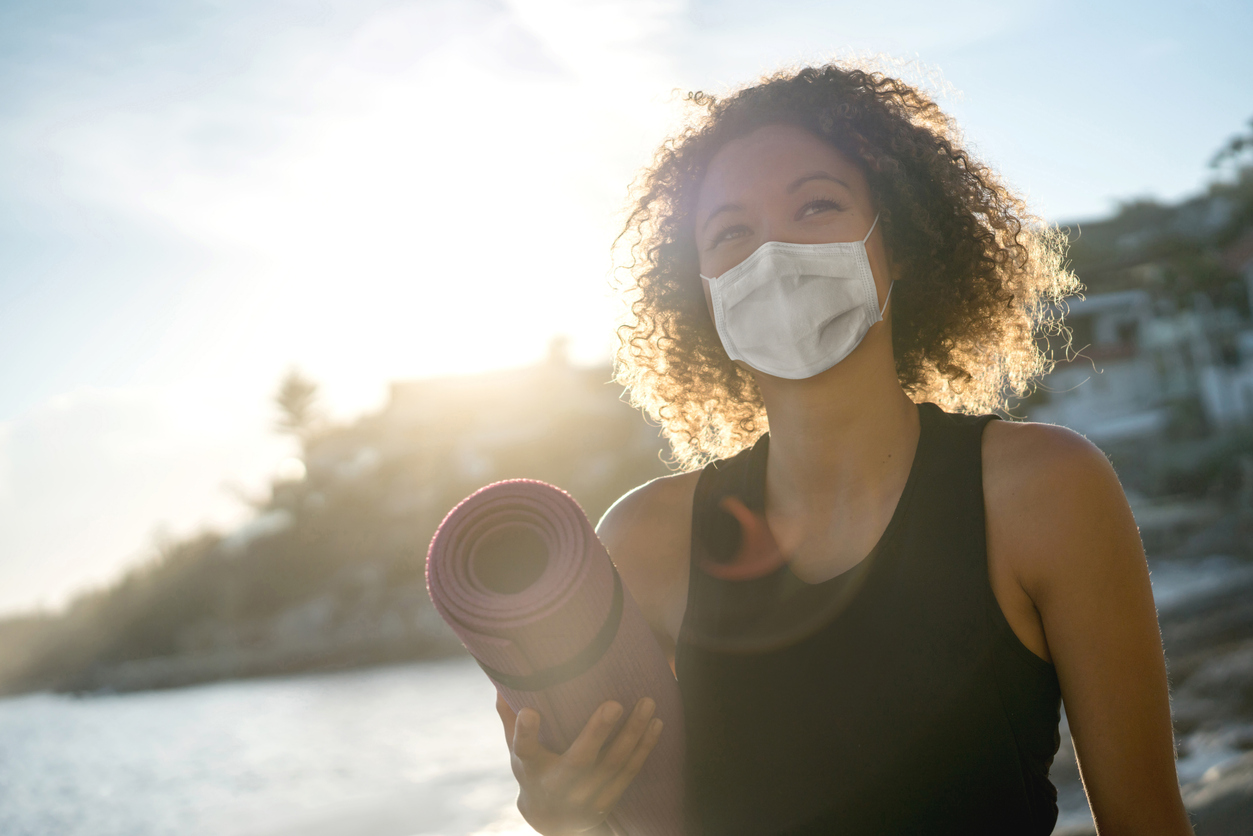 Woman wearing a COVID mask and holding a yoga mat
