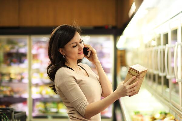 A woman grocery shopping while on her smartphone