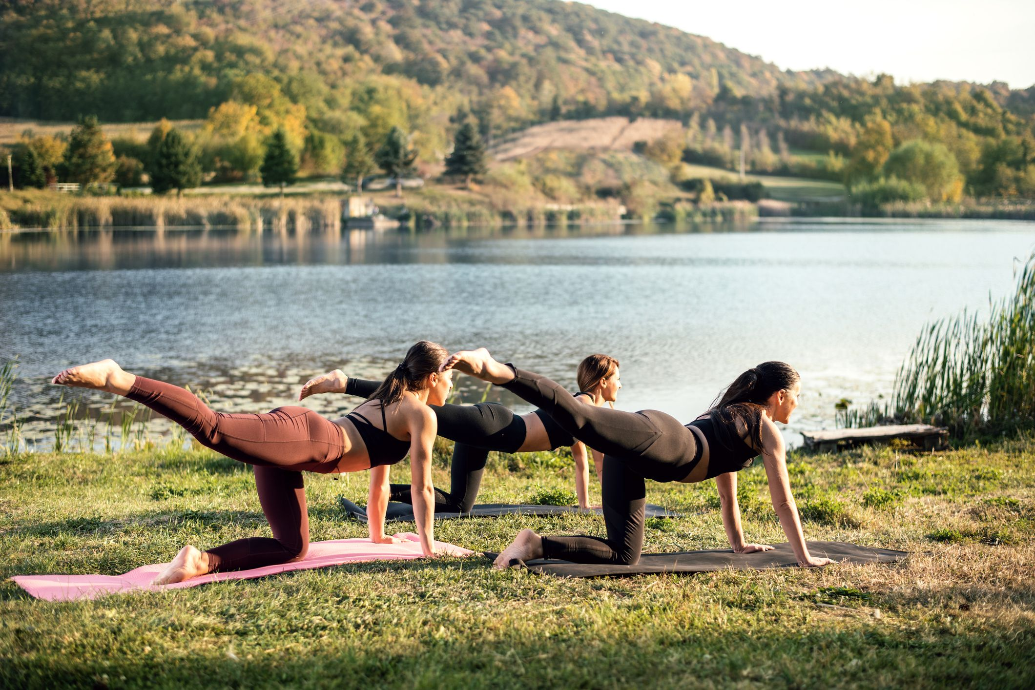 Women doing yoga by a lake