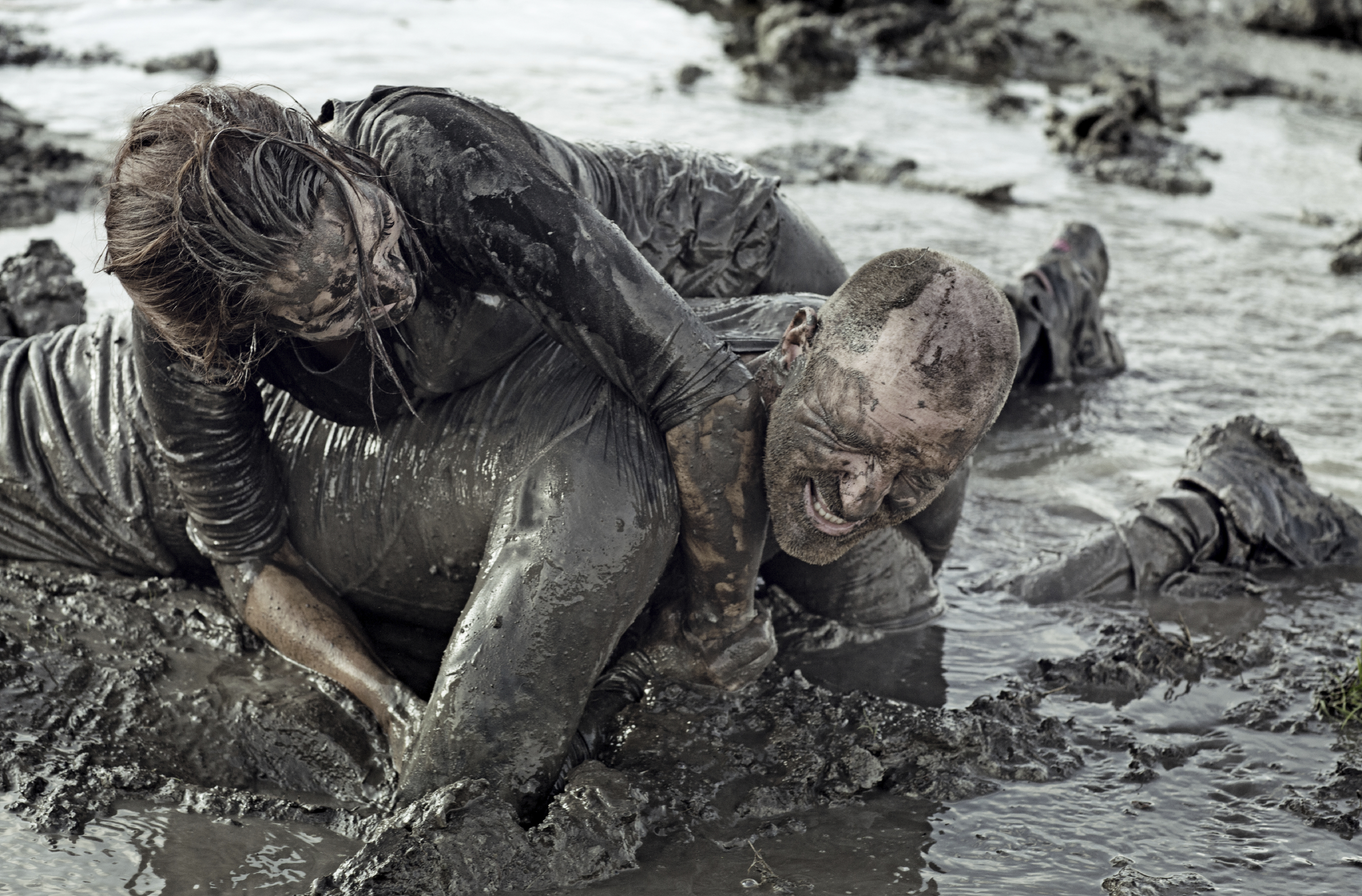 Young couple wrestling in the mud