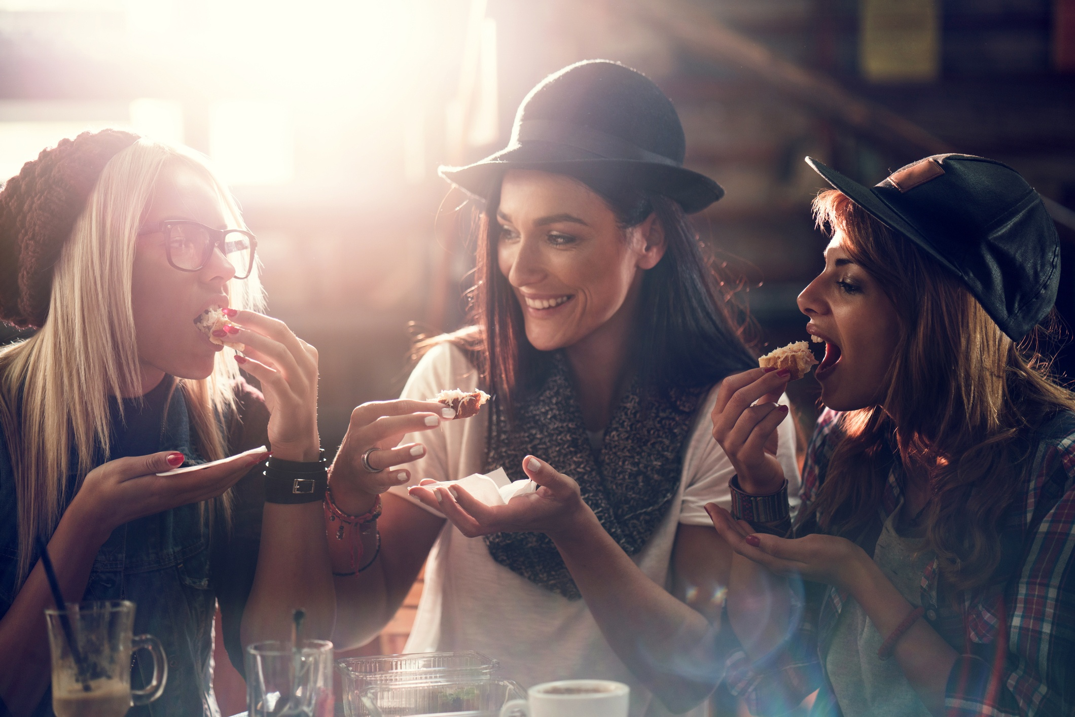 Young-female-friends-having-a-snack-in-a-cafe.-498891264_2123x1416-1