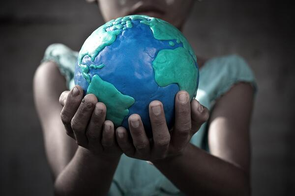 Young girl holding a globe she molded from clay