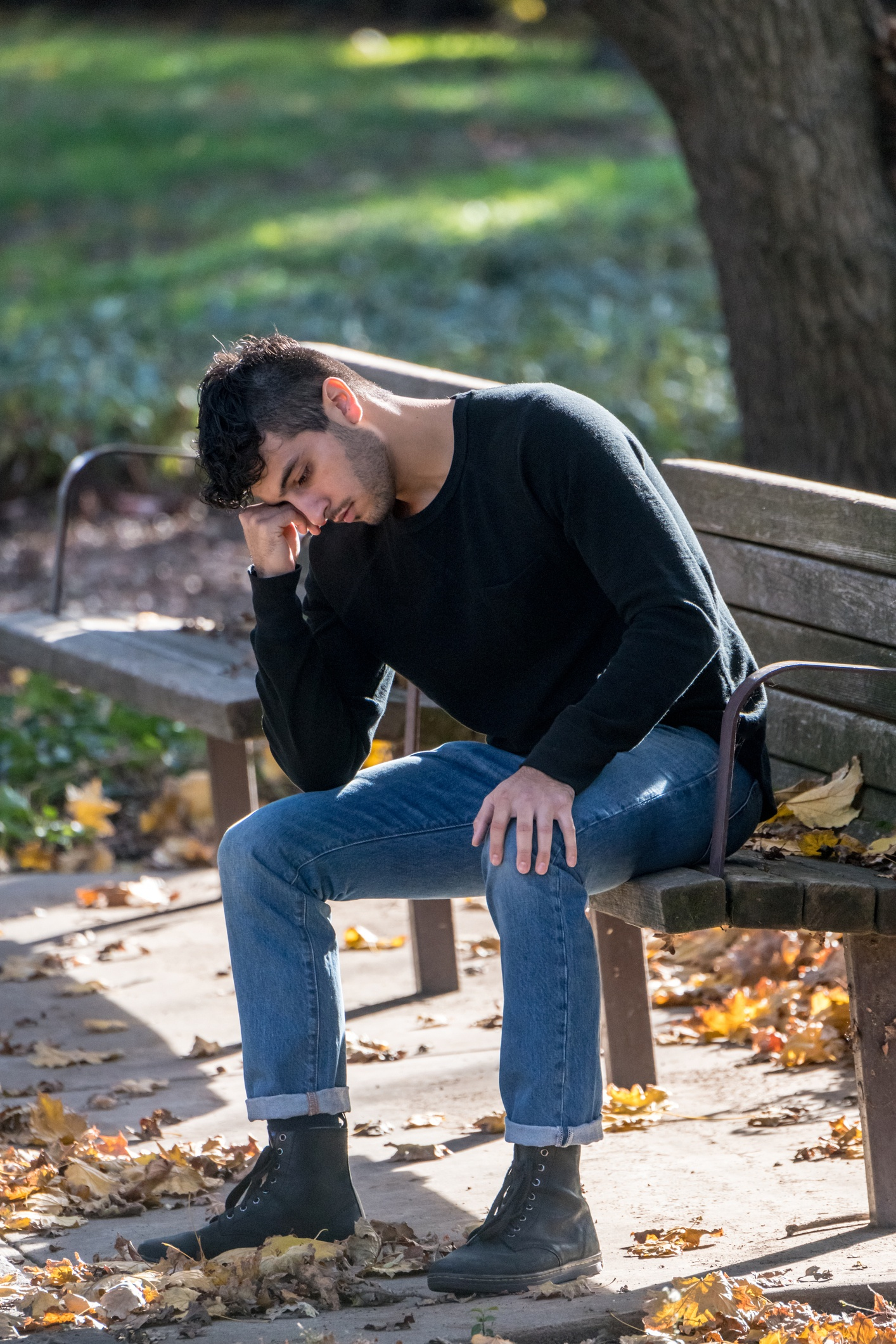 Young man on a park bench feeling sad and seeking resolution