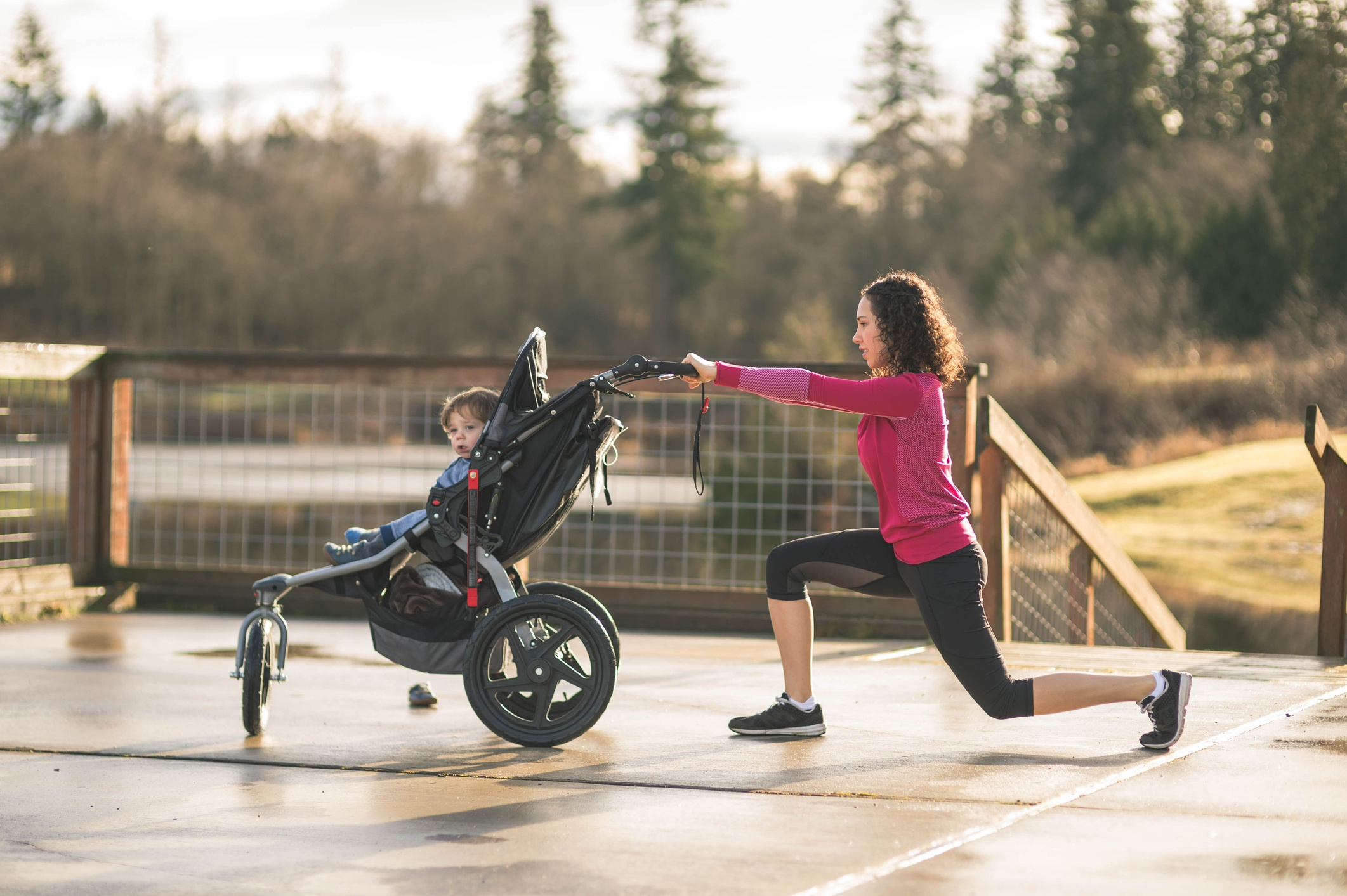 Young-mom-stretching-next-to-child-in-baby-stroller-647549370_2126x1415