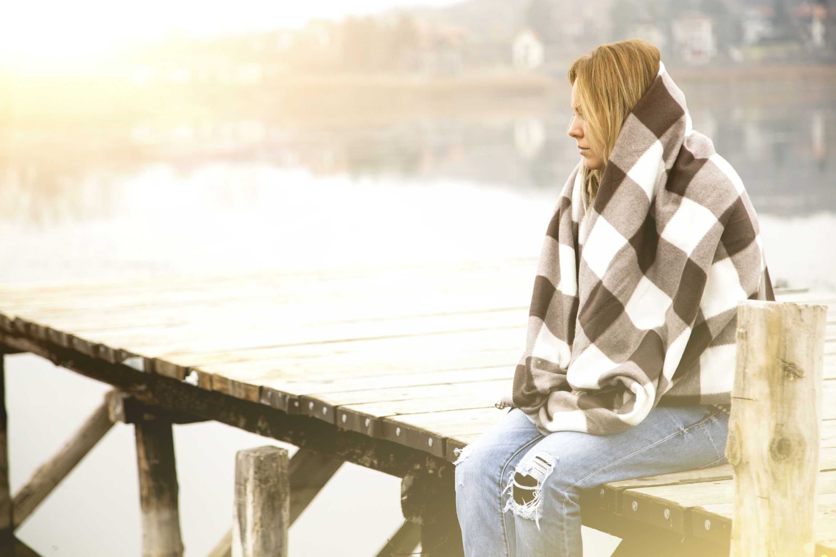 A young woman feels sadness as she sits on a dock