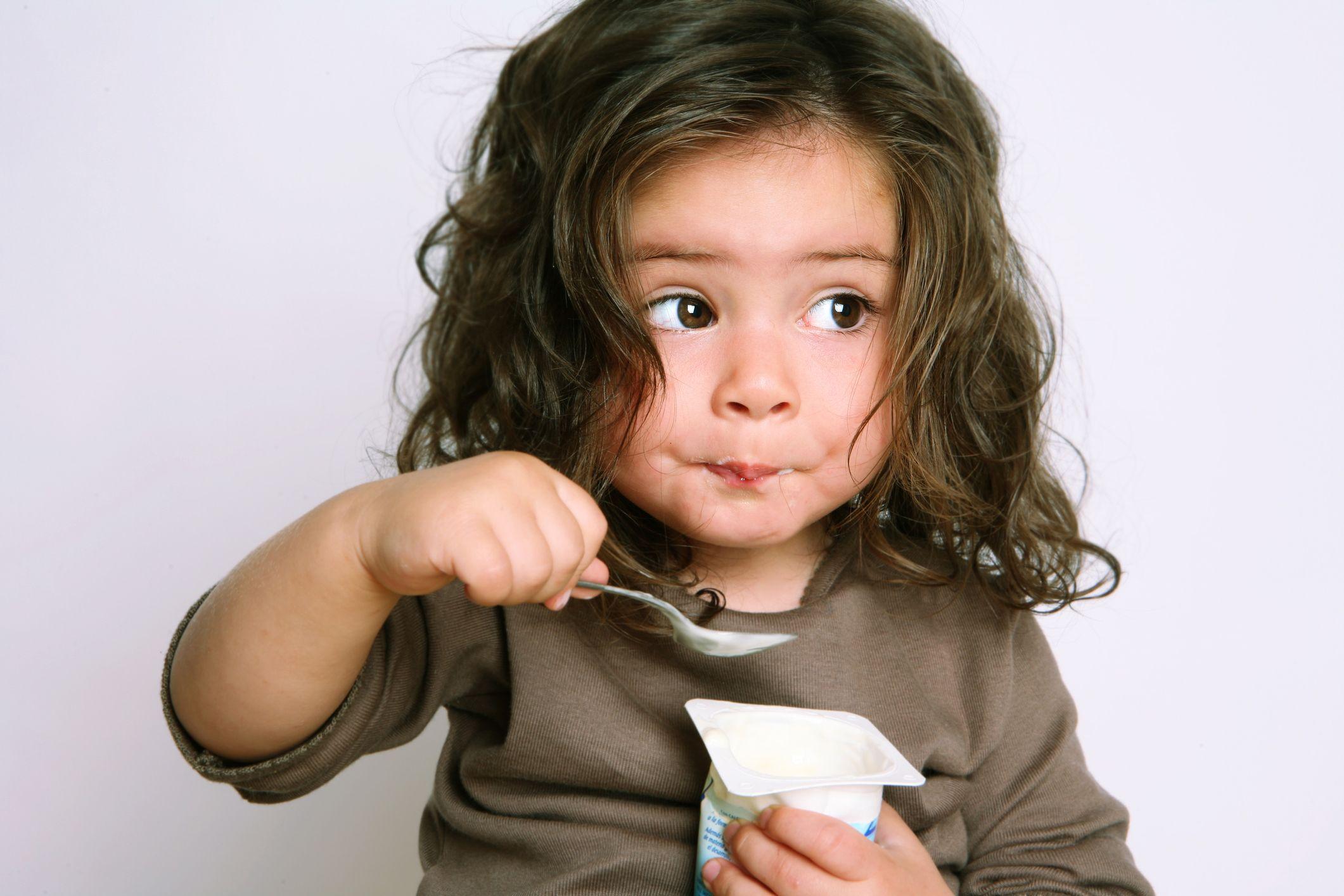 Little girl eating yogurt enthusiastically
