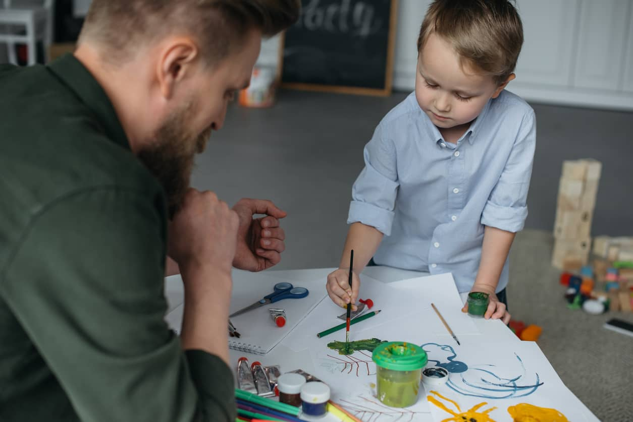 Little boy paining to self-calm with father present