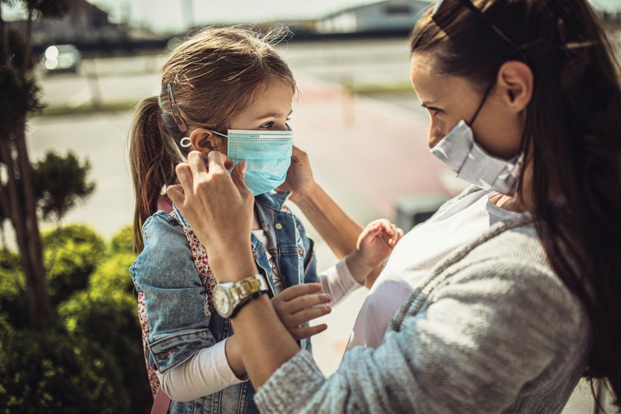 Mother adjusting a COVID mask on her daughter
