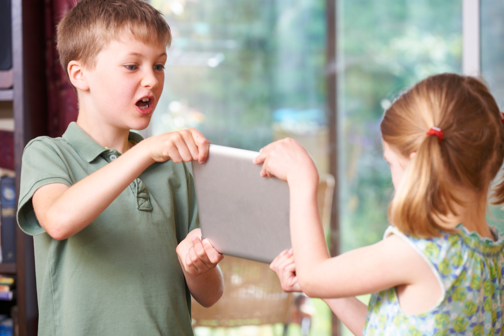 Boy and girl fighting over a iPad