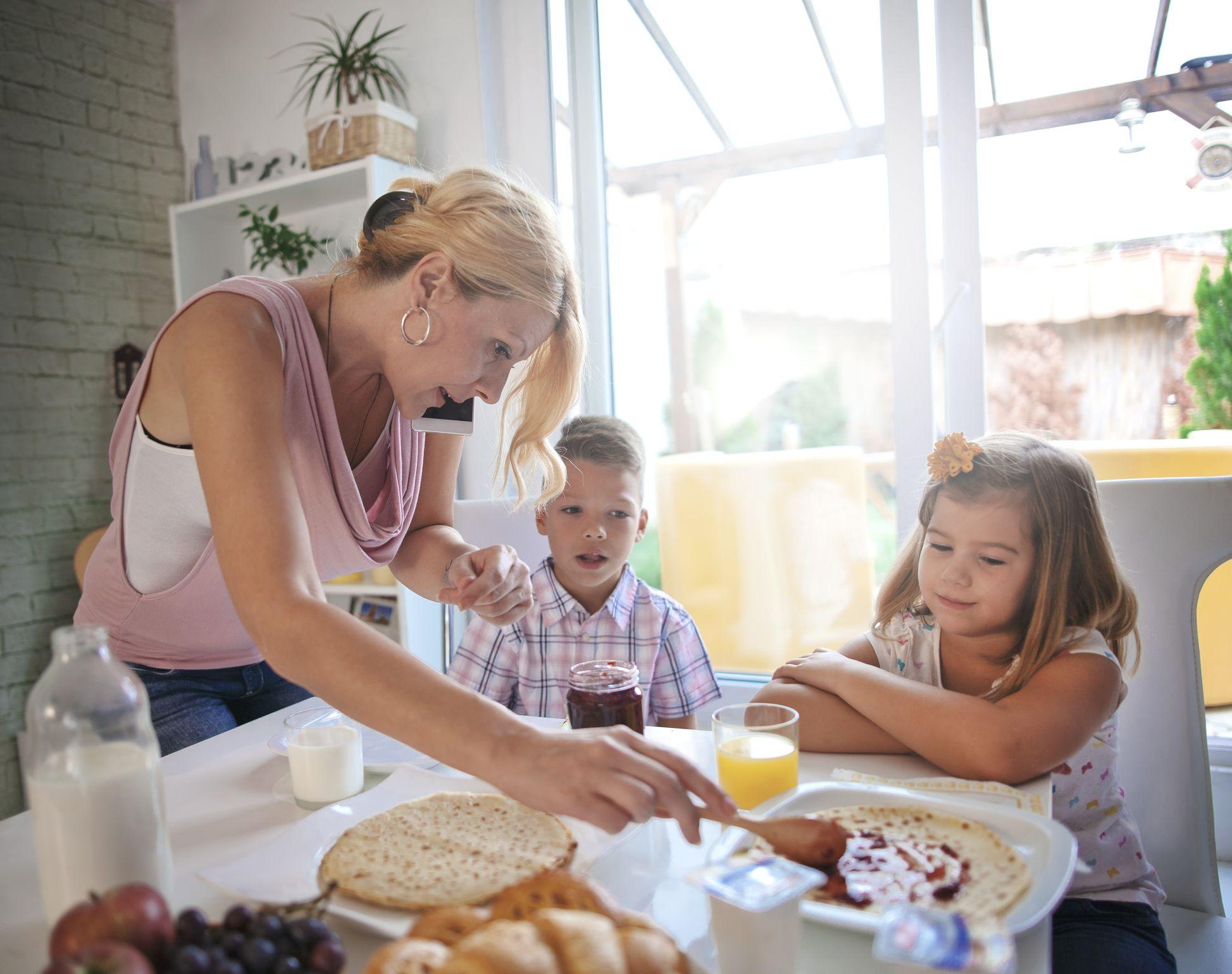 Mother serving breakfast while multitasking