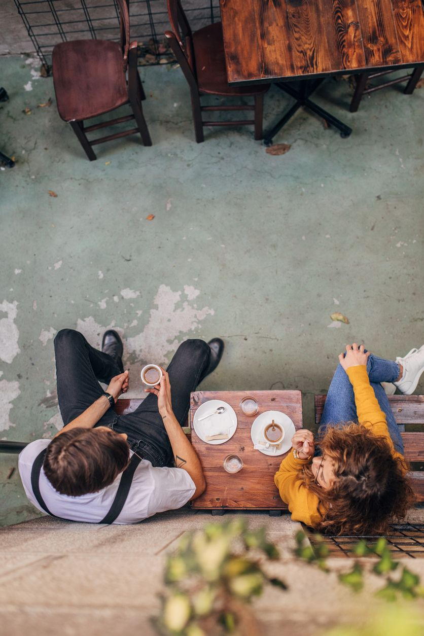 Couple-sitting-in-sidewalk-cafe-1169731553_838x1257-compressor