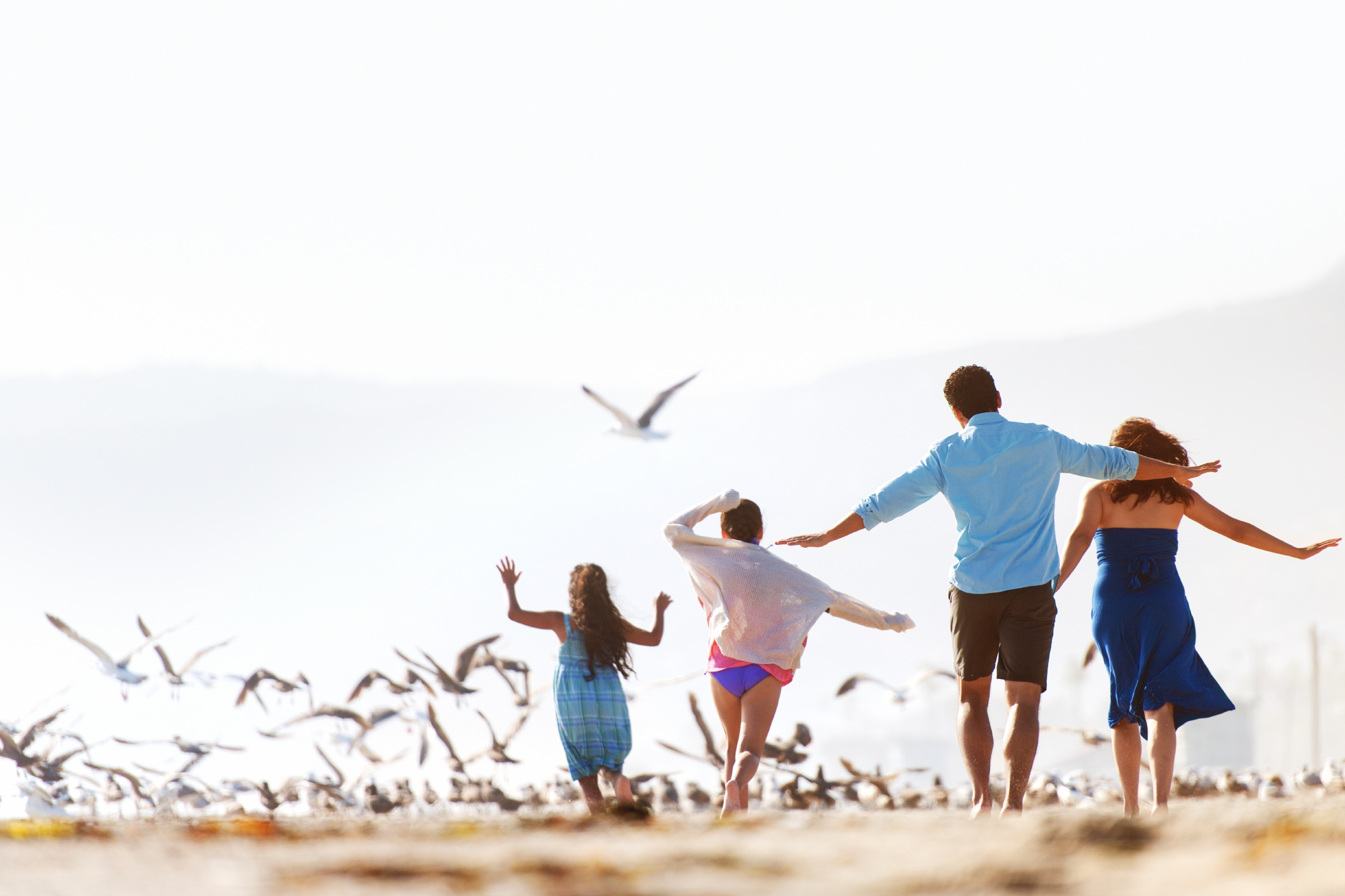 Family running on the the beach together