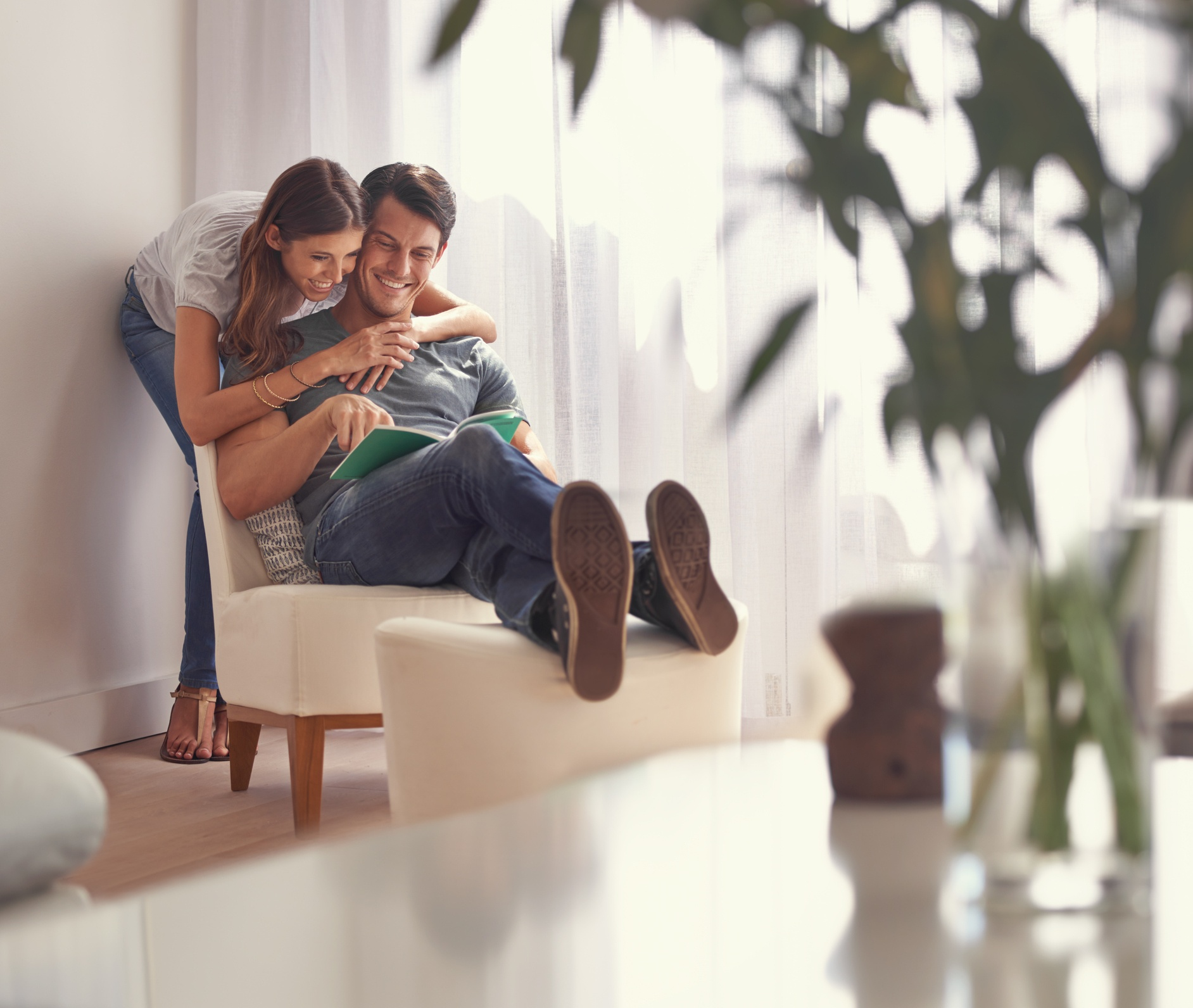 Woman hugging and appreciating her partner while he is reading