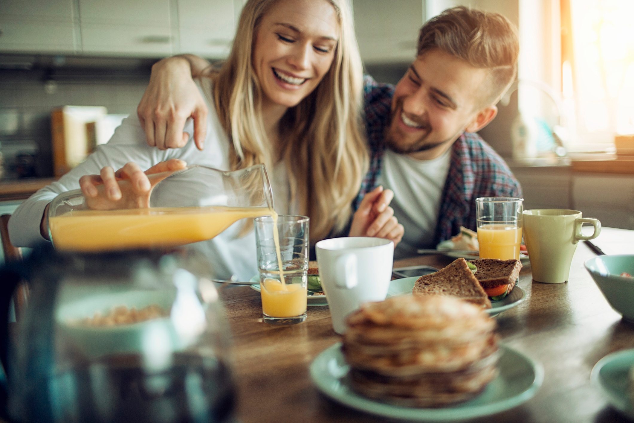 Young couple having breakfast together laughing